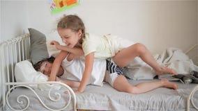 Il ragazzo getta un cuscino alla ragazza che dorme, al fratello felice ed alla sorella di risata che hanno una lotta di cuscino archivi video