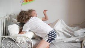 Il ragazzo getta un cuscino alla ragazza che dorme, al fratello felice ed alla sorella di risata che hanno una lotta di cuscino stock footage