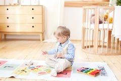Il ragazzo gioca con i giocattoli di legno a casa Giocattoli di legno educativi per il bambino Ritratto di un ragazzo che si sied fotografie stock