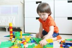 Il ragazzo gioca i blocchi di plastica Fotografia Stock Libera da Diritti