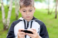 Il ragazzo gioca su un telefono cellulare in un parco Fotografie Stock Libere da Diritti