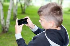 Il ragazzo gioca su un telefono cellulare in un parco Fotografie Stock