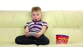 Il ragazzo gioca sul gioco online del telefono, mangia il popcorn Movimento lento video d archivio