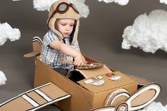 Il ragazzo gioca in un aeroplano fatto della scatola di cartone e dei sogni di diventare un pilota, nuvole da ovatta su un fondo  fotografie stock libere da diritti