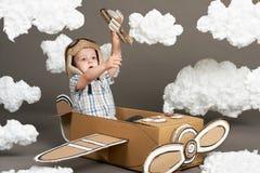 Il ragazzo gioca in un aeroplano fatto della scatola di cartone e dei sogni di diventare un pilota, nuvole da ovatta su un fondo  fotografia stock libera da diritti