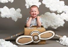 Il ragazzo gioca in un aeroplano fatto della scatola di cartone e dei sogni di diventare un pilota, nuvole da ovatta su un fondo  immagini stock libere da diritti