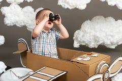 Il ragazzo gioca in un aeroplano fatto della scatola di cartone e dei sogni di diventare un pilota, nuvole da ovatta su un fondo  immagine stock libera da diritti