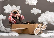 Il ragazzo gioca in un aeroplano fatto della scatola di cartone e dei sogni di diventare un pilota, nuvole di ovatta su un fondo  immagine stock libera da diritti