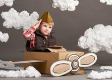 Il ragazzo gioca in un aeroplano fatto della scatola di cartone e dei sogni di diventare un pilota, nuvole di ovatta su un fondo  immagini stock