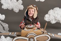 Il ragazzo gioca in un aeroplano fatto della scatola di cartone e dei sogni di diventare un pilota, nuvole di ovatta su un fondo  fotografie stock