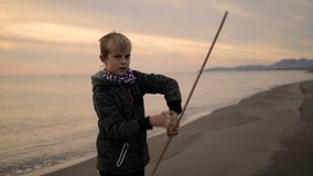 Il ragazzo gira il bastone in sue mani mentre sta sulla spiaggia al tramonto archivi video