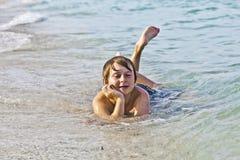 Il ragazzo gode di di trovarsi alla spiaggia nella spuma Fotografie Stock Libere da Diritti