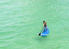 Il ragazzo gode di sta sulla pagaia che pratica il surfing nell'oceano fotografia stock