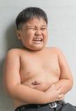 Il ragazzo grasso asiatico ha mal di stomaco Immagine Stock