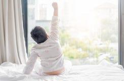Il ragazzo grasso obeso in pigiami sta sedendosi sul letto Immagini Stock