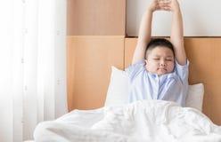 Il ragazzo grasso obeso sveglia ed allungando sul letto Immagine Stock Libera da Diritti