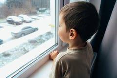 Il ragazzo guarda fuori la finestra immagine stock