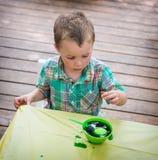Il ragazzo guarda il suo uovo di Pasqua nella tintura verde Fotografie Stock Libere da Diritti