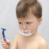 Il ragazzo guarda in perdita per il rasoio Fotografie Stock Libere da Diritti