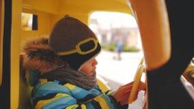 Il ragazzo guida un'automobile del giocattolo su un girotondo in un cappuccio del casco stock footage