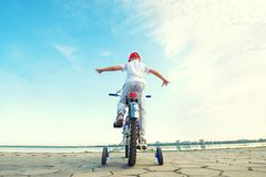 Il ragazzo guida una bicicletta sul lungomare fotografie stock