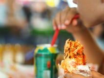 Il ragazzo ha alimentato il pane degli alimenti a rapida preparazione con la sue mano ed anche bevanda fotografie stock