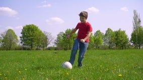 Il ragazzo ha colpito la palla sul prato verde, movimento lento video d archivio