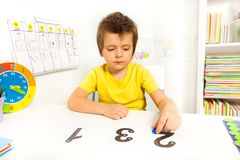 Il ragazzo impara contare le monete messe sui numeri Immagini Stock