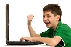 Il ragazzo impressionabile sta giocando il gioco di computer immagini stock libere da diritti