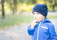 Il ragazzo infantile mette le sue dita nella sua bocca Fotografia Stock
