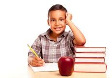 Il ragazzo ispanico adorabile con i libri, Apple, disegna a matita Immagine Stock