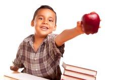 Il ragazzo ispanico adorabile con i libri, Apple, disegna a matita Immagine Stock Libera da Diritti