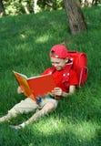 il ragazzo legge il manuale di seduta fotografia stock libera da diritti