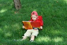 il ragazzo legge il manuale di seduta immagini stock