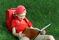 il ragazzo legge il manuale di seduta fotografie stock libere da diritti
