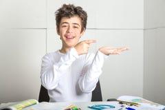 Il ragazzo liscio-pelato Caucasian affidabile indica qualcosa sulla sua h Fotografia Stock