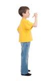 Il ragazzo in maglietta gialla scrive Fotografie Stock Libere da Diritti
