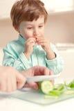 Il ragazzo mangia il cetriolo Fotografia Stock Libera da Diritti