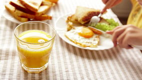 Il ragazzo mangia la sua prima colazione che consiste di un uovo fritto, di un certo pane tostato e del succo d'arancia archivi video