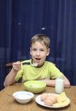 Il ragazzo mangia un porridge con latte Immagini Stock