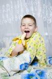 Il ragazzo mangia una banana Fotografia Stock Libera da Diritti