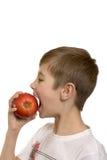 Il ragazzo mangia una mela Fotografia Stock