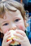Il ragazzo mangia una mela Fotografia Stock Libera da Diritti