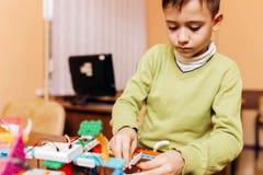 Il ragazzo messo a fuoco vestito in maglione verde si siede alla tavola nella scuola di robotica e fa un robot dal robot fotografie stock libere da diritti
