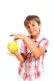 Il ragazzo mette la moneta nella banca piggy Immagini Stock