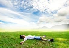 Il ragazzo mette sull'erba che il tatto si rilassa immagine stock