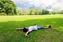 Il ragazzo mette sull'erba che il tatto si rilassa immagine stock libera da diritti