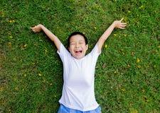 Il ragazzo mette sull'erba che il tatto si rilassa fotografia stock