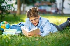 Il ragazzo molto sveglio e giovane in vetri rotondi e la camicia blu legge il libro che si trova sull'erba accanto allo zaino ed  immagine stock