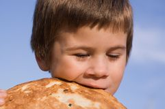 Il ragazzo morde il pane Fotografia Stock